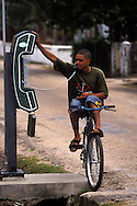 BELIZE / Belize City / Young cyclist using a public telephone...© JOAN COSTA