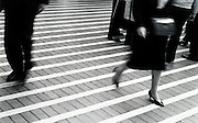 A business woman walking quickly down a striped street
