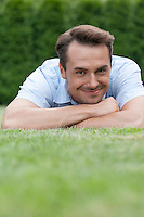 Portrait of smiling young man lying on grass in park