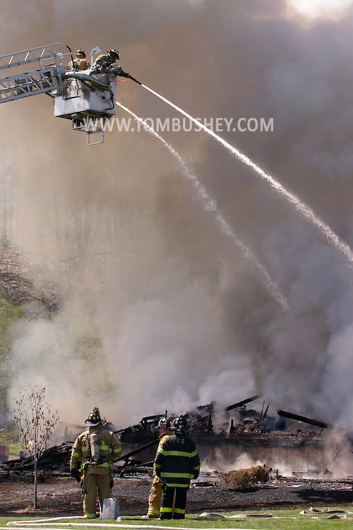 Goshen, N.Y. - Two firefighters on a ladder truck spray water on a fire that destroyed a two-story house on April 29, 2006, as other firefighters look at the smoking rubble. ©Tom Bushey