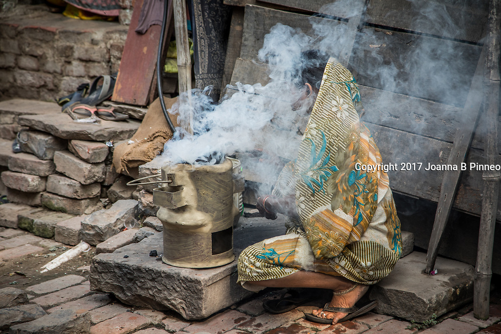 Varanasi, India. A woman prepares her coal pot to set up to make morning tea where small shops near the River Ganges open for local residents and tourists. According to The Energy and Resources Institute (TERI), nearly 40% of India's air pollution comes from domestic fuel burning.