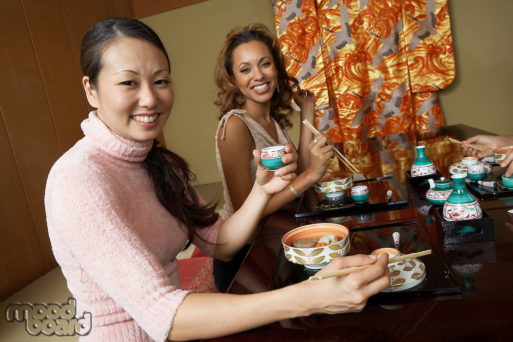 Young people holding saki cups in Japanese restaurant