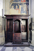 confessional with damaged fresco painting Arezzo Italy