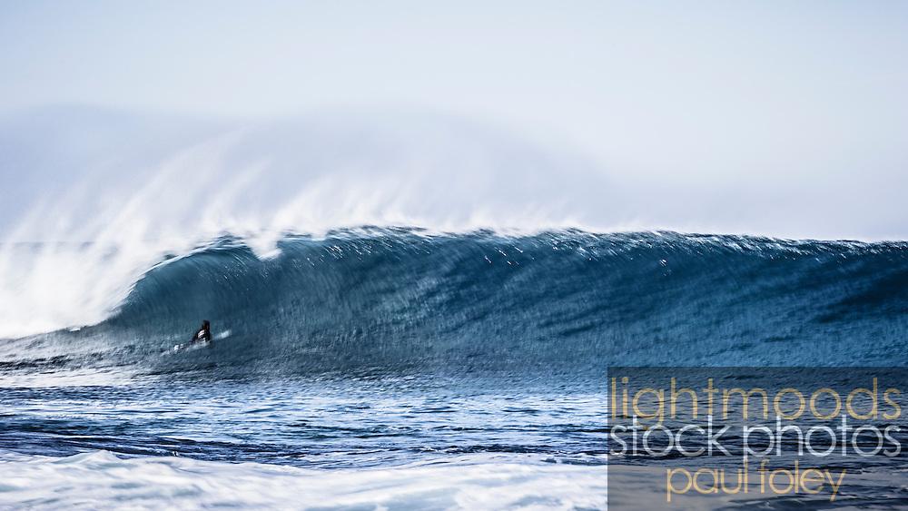 Surfer pushing through breaking wave with speed blur.