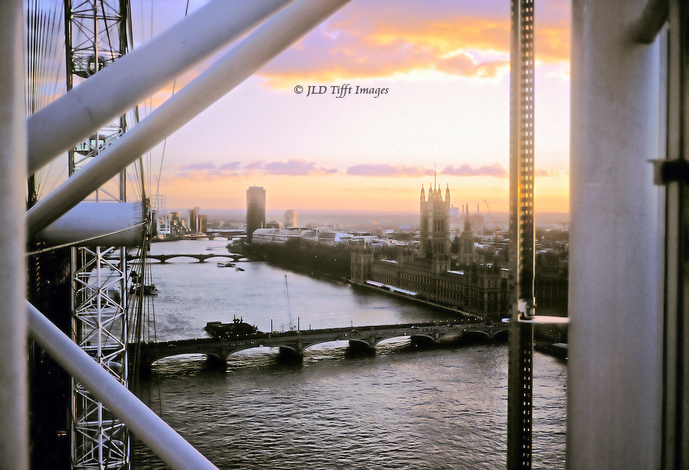 London at sunset: view west along the Thames from the top of the London Eye.  Houses of Parliament and Westminster Bridge in view, along with some of the metal struts of the wheel.