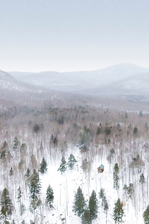A solitary cabin in the remote, wintery mountains of rural Quebec.