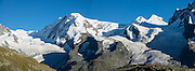 Monte Rosa massif / Dufourspitze (4634 m / 15,203 ft, second-highest mountain of the Alps and highest of Switzerland) and Castor & Pollux seen from Rotenboden, in the Pennine/Valais Alps, Europe. In Zermatt, the Gornergrat rack railway (GGB) takes you to a spectacular ridge (at 3135 m or 10,285 ft) between Gornergletscher and Findelgletscher. Gornergrat train, opened in 1898, climbs almost 1500 m or 4900 ft. Gornergrat train, opened in 1898, climbs almost 1500 m or 4900 ft via Riffelalp and Riffelberg. This image was stitched from multiple overlapping photos.
