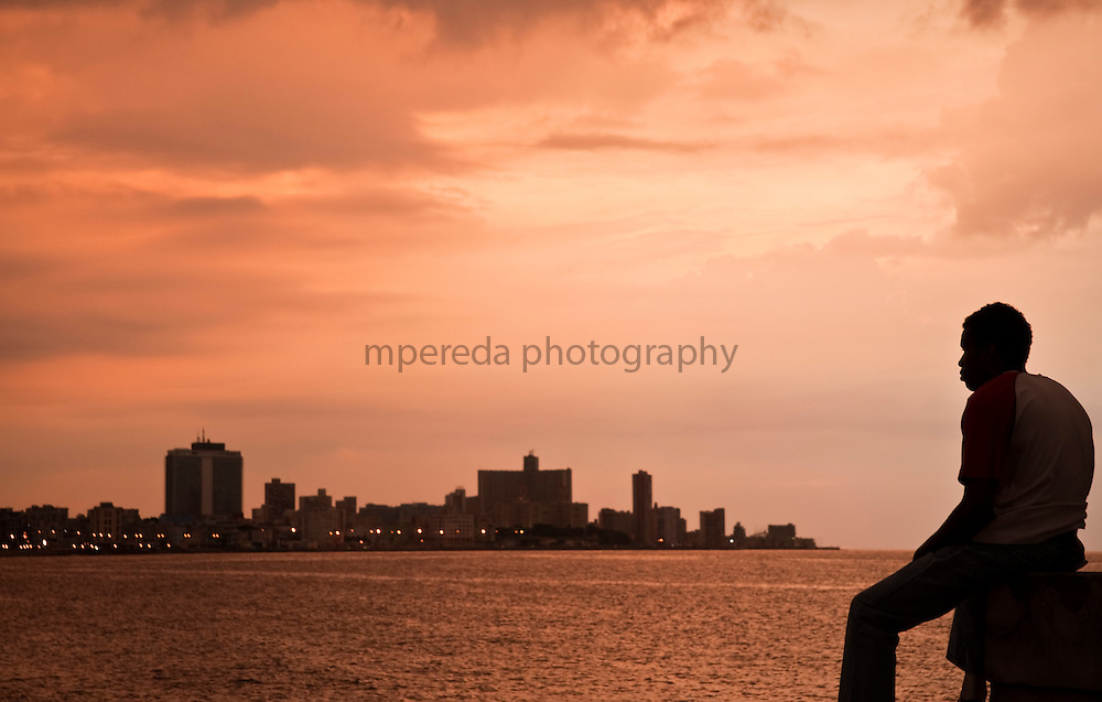 CUBA (La Habana). 2009. Dusk in Malecon. Lots of young people reckon that emigration is the only way to scape of the problems of the county.