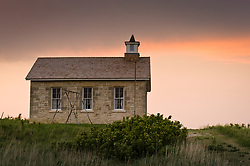 Evening sunset light bathes the skies over the Lower Fox Creek Schoolhouse located in the Tallgrass Prairie National Preserve in the Kansas Flint Hills. The school, on the National Historic Register of Historic Places, was built on land donated by cattleman Stephen F. Jones. Built in 1882, the one-room school had its first classes in 1884. Typical enrollment was between one to 19 students of all grades. The school was closed in 1930 and restored in 1968 by the Garden Clubs in the Mid-East District of Kansas. The 10,894-acre Tallgrass Prairie National Preserve is located in Chase County near the towns of Strong City and Cottonwood Falls. Less than four percent of the original 140 million acres of tallgrass prairie remains in North America. Most of the remaining tallgrass prairie is in the Flint Hills in Kansas. Tallgrass Prairie National Preserve is the only unit of the National Park Service dedicated to the preservation of the tallgrass prairie ecosystem. The Tallgrass Prairie National Preserve is co-managed with The Nature Conservancy.