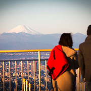 TOKYO, JAPAN - JANUARY 1 : A couple look at Mount Fuji during the New Year's first sunrise on Sunday, January 1, 2016, in the observation deck of MORI building in central Tokyo, Japan. Japan celebrated the start of 2017 for the Year of the Rooster.  (Photo by Richard Atrero de Guzman/NURPhoto)