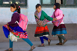South America, Peru, Vicos, 3 school girls in traditional clothing outside classroom