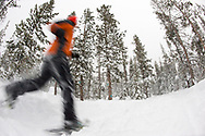 Low angle view of a young woman wearing snowshoes running in the snow in a forest in Bend, Oregon. (releasecode: jk_mr1033) (Model Released)