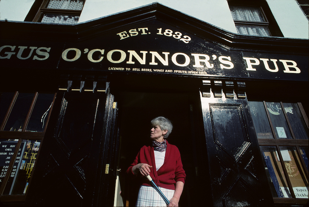 Europe, Ireland, County Galway, Doolin, Pub matron washes front of O'Connor's Pub on autumn morning