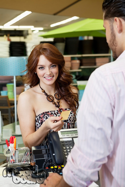 Portrait of a happy young woman paying through credit card in store
