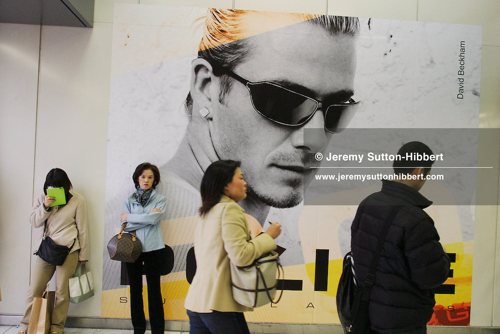 DAVID BECKHAM ADVERTISING, TOKYO, JAPAN. advertising poster for 'Police' sunglasses featuring David Beckham covers a wall in a Tokyo train station. Beckham, style icon, football player for England and Real Madrid, advertises many products in Asia, most obviously in Tokyo. His recent 5 day visit to the city is rumoured to have earned him approximately 5 million pounds sterling in advertising fees, for products such as mobile phones, chocolate, and car engine oil.