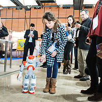 Lyon, France - 19 March 2014: Elora, 8, walks hand by hand with NAO Robot by Aldebaran at Innorobo 2014, the biggest fair in Europe for robotics.