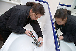 Plumber using pliers to fix a bathroom tap,