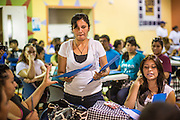 """18 AUGUST 2012 - PHOENIX, AZ:  A volunteer hands out information packets at the deferred action workshop in Phoenix. More than 1000 people attended a series of 90 minute workshops in Phoenix Saturday on the """"deferred action"""" announced by President Obama in June. Under the plan, young people brought to the US without papers, would under certain circumstances, not be subject to deportation. The plan mirrors some aspects the DREAM Act (acronym for Development, Relief, and Education for Alien Minors), that immigration advocates have sought for years. The workshops were sponsored by No DREAM Deferred Coalition. PHOTO BY JACK KURTZ"""