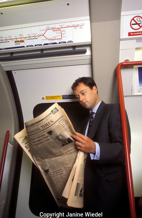 Commuter reading financial Times on underground