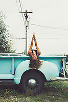 Woman playing yoga in an old Chevy truck.