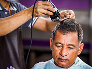 12 SEPTEMBER 2018 - BANGKOK, THAILAND: A barber gives a man a haircut at Hua Lamphong train station in Bangkok. Barber schools set up in the station and offer free haircuts to travelers.     PHOTO BY JACK KURTZ