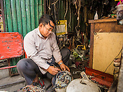 24 FEBRUARY 2015 - PHNOM PENH, CAMBODIA: A man repairs rice cookers in his shop in the White Building. The White Building, the first modern apartment building in Phnom Penh, originally had 468 apartments, and was opened the early 1960s. The project was overseen by Vann Molyvann, the first Cambodian architect educated in France. The building was abandoned during the Khmer Rouge occupation. After the Khmer Rouge were expelled from Phnom Penh in 1979, artists and dancers moved into the White Building. Now about 2,500 people, mostly urban and working poor, live in the building. Ownership of the building is in dispute. No single entity owns the building, some units are owned by their occupants, others units are owned by companies who lease out apartments. Many of the original apartments have been subdivided since the building opened and serve as homes to two or three families. The building has not been renovated since the early 1970s and is in disrepair. Phnom Penh officials have tried to evict the tenants and demolish the building but residents refuse to move out.   PHOTO BY JACK KURTZ