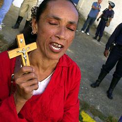 A supporter of Venezuelen President Hugo Chavez prays for a peacefule end to Venezuela's crisis, Dec 16, 2002, outside the Brigada Motorizada Police station.
