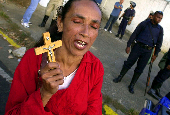 A supporter of Venezuelen President Hugo Chavez prays for a peacefule end to Venezuela's crisis, Dec 16, 2002, outside the Brigada Motorizada Police station.