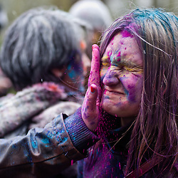 London, UK - 23 March 2013: a girl has her face covered with colored powder during the Holi Spring Festival of Colour takes place at Orleans House Gallery in Twickenham. The annual event marks the end of Winter and welcomes the joy of spring.