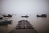 Fishing boats and a broken pier near the river in Hoi An, Vietnam.