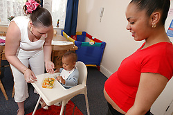Pregnant young woman watching her friend feeding her baby in a high chair,