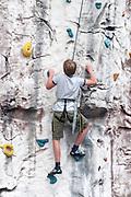 Young teen boy climbs up an artificial climbing wall