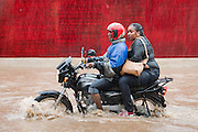 Dar es Salaam, Tanzania 4/28/16 - A motorcyclist and his passenger brave flooded United Nations Road in Dar es Salaam, Tanzania on April 28, 2016. The Tanzania Meteorological Agency says several days of heavy rain have been caused by remnants of tropical cyclone Fantala.  Photo by Daniel Hayduk