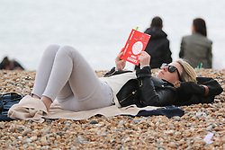 © Licensed to London News Pictures. 23/05/2015. Brighton, UK. A woman reads a book on the beach in Brighton, today May Bank Holiday Weekend, today May 23rd 2015. Photo credit : Hugo Michiels/LNP