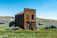 Two visitors peek in a window of the Swazey Hotel structure still standing, though leaning, at Bodie State Historic Park and ghost town.