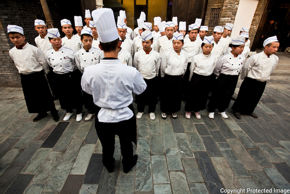 Cooks and waiters getting instructions outside a restaurant in Chengdu