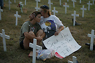 A Camp Casey II during the Cindy Sheehan Vigil, Joyce Swan, left, is embraced by her mother Bell McBride while sitting among hundreds of crosses representing U.S. service men and women who have died during the war in Iraq