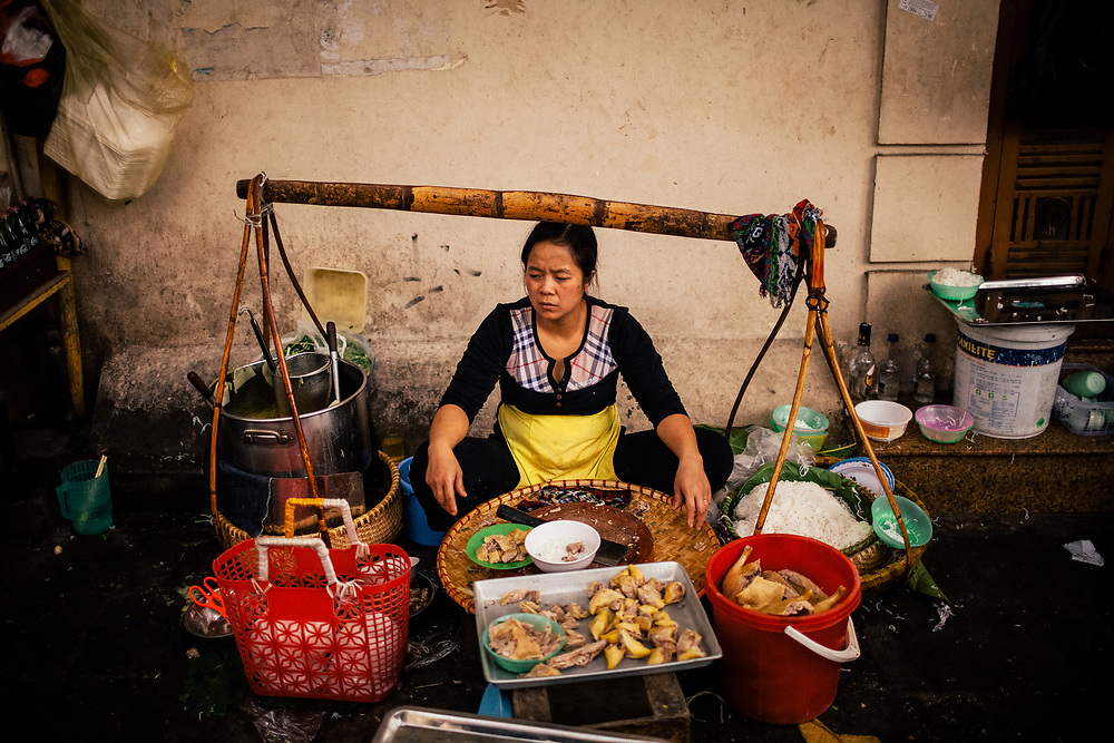 A street side noodle vendor takes a brief break during the lunch rush in Hanoi, Vietnam.