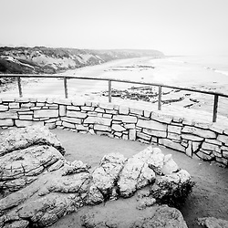 Laguna Beach Crystal Cove State Park scenic overlook railing with the beach and Pacific Ocean in black and white