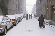 4 people walking down narrow street in snow
