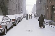 4 people walking down narrow street in snow
