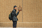 A Chinese man smokes a cigarette holding his songbird cage at the Yuen Po Street Bird Garden in Mong Kok, Kowloon, Hong Kong.