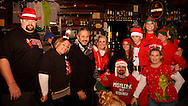 Some of the early participants gather for a group photo at the Dublin Pub, the first stop of the Santa Pub Crawl through the Historic Oregon District near downtown Dayton, Saturday, December 10, 2011.