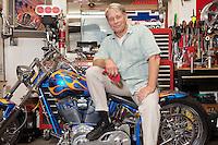 Senior man sitting on motorcycle in workshop
