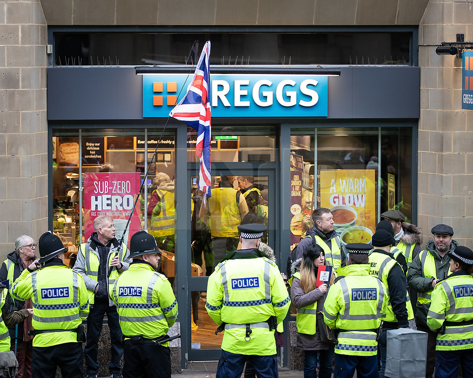 "© Licensed to London News Pictures . 05/01/2019. Manchester, UK. Protesters are kettled by police outside a branch of Greggs the baker on Mosley Street . A Yellow Vest demonstration takes place in central Manchester . The protest was organised via YouTube account "" Tommy Robinson News "" and was called in the wake of stabbings at Manchester Victoria Train Station on New Year's Eve . Protesters chanted in favour of Brexit , against police and press and carried pro-Trump and EDL clothing and placards . Photo credit : Joel Goodman/LNP"