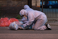 © Licensed to London News Pictures. 25/07/2017. LONDON, UK.  Police forensic officers at the crime scene cordon on Burnham Road just off Roman Road this evening near Singh supermarket.  Two males in their late teens have been taken to hospital for treatment after an unknown liquid was thrown at them. Photo credit: Vickie Flores/LNP