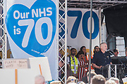 Jeremy Corbyn addresses the crowd with a signer - #OurNHS70: free, for all, forever a protest and celebration march in honour of the 70 year history of the National Health Service. Organised by: The People's Assembly, Trades Union Congress, Unison, Unite, GMB, British Medical Association, Royal College of Nursing, Royal College of Midwives amongst others.