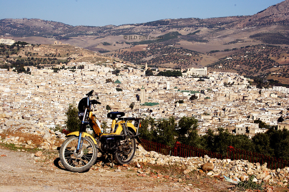 View of the Fes medina from the hill opposite.  A motorbike is parked in the foreground.  The ancient town gleams white under the sun.  Bare and patchy forested hills rise up in the distance.