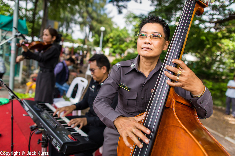 "15 JUNE 2014 - BANGKOK, THAILAND:  A Thai police jazz trio performs on a stage during a ""Return Happiness to Thais"" party in Lumpini Park in Bangkok. The Thai military junta, formally called the National Council for Peace and Order (NCPO), is sponsoring a series of events throughout Thailand to restore ""Happiness to Thais."" The events feature live music, dancing girls, military and police choirs, health screenings and free food.  PHOTO BY JACK KURTZ"