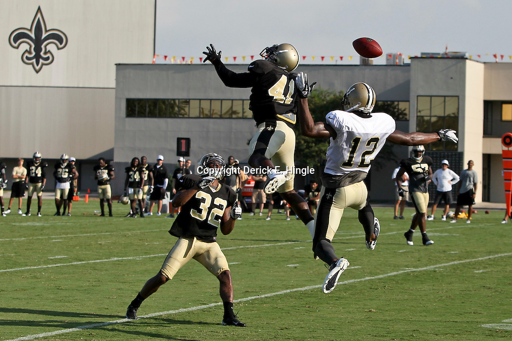 July 29, 2012; Metairie, LA, USA; New Orleans Saints defenders safety Roman Harper (41) and cornerback Johnny Patrick (32) break up a pass intended for wide receiver Marques Colston (12) during a training camp practice at the team's practice facility. Mandatory Credit: Derick E. Hingle-US PRESSWIRE